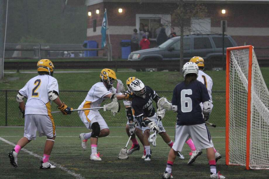 The Weston boys lacrosse team, white uniforms, play aggressive defense against Staples. Weston won 7-6 at Byram Hills, N.Y. for its fifth straight win. Photo: Sharon Furbee / Contributed Phot