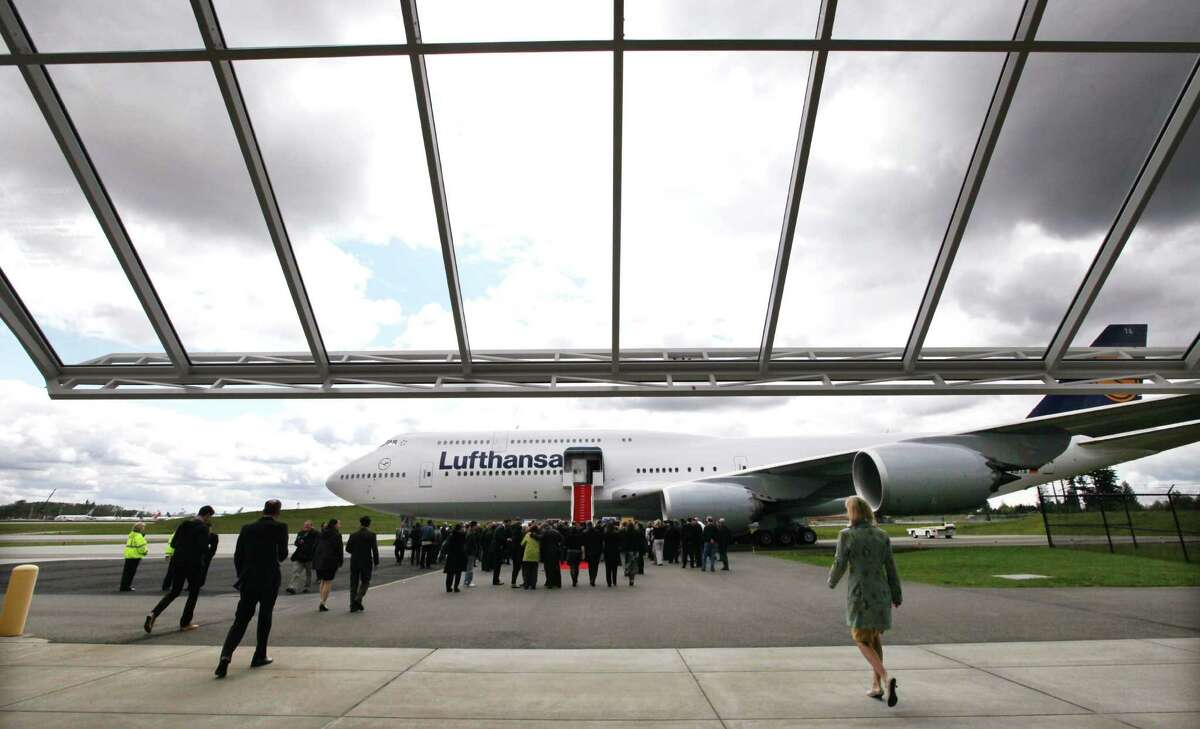 Guests walk toward the first Boeing 747-8 Intercontinental for launch airline Lufthansa following a delivery ceremony on Tuesday, May 1, 2012, in the Future of Flight Aviation Center in Mukilteo, Wash.