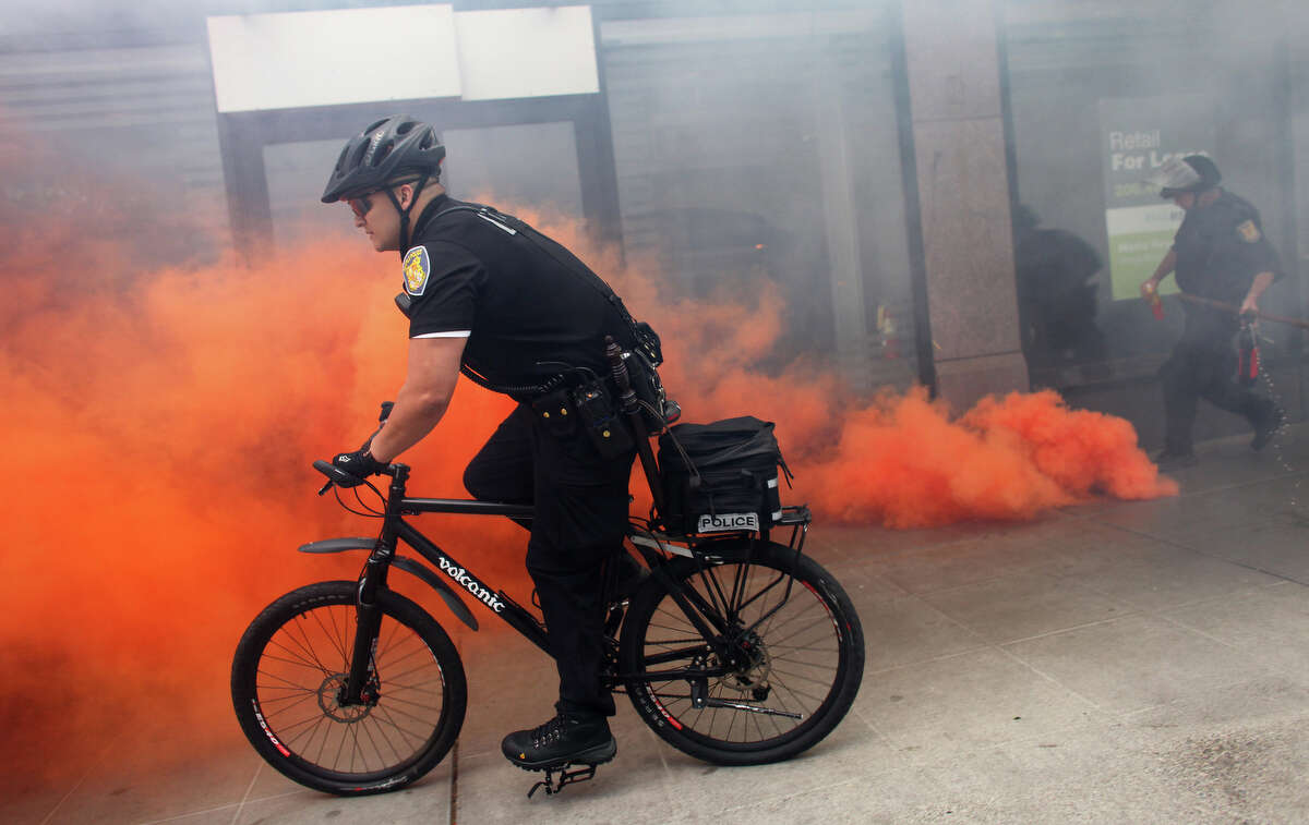A Seattle police officer rides past a smoke bomb as black-clad protesters break windows of downtown businesses during a May Day rally in Seattle.