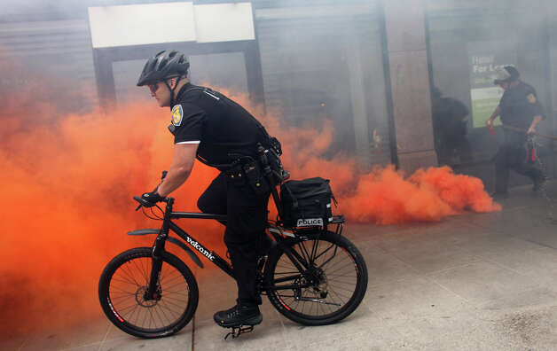 A Seattle police officer rides past a smoke bomb as black-clad protesters break windows of downtown businesses during a May Day rally in Seattle. Photo: JOSHUA TRUJILLO / SEATTLEPI.COM