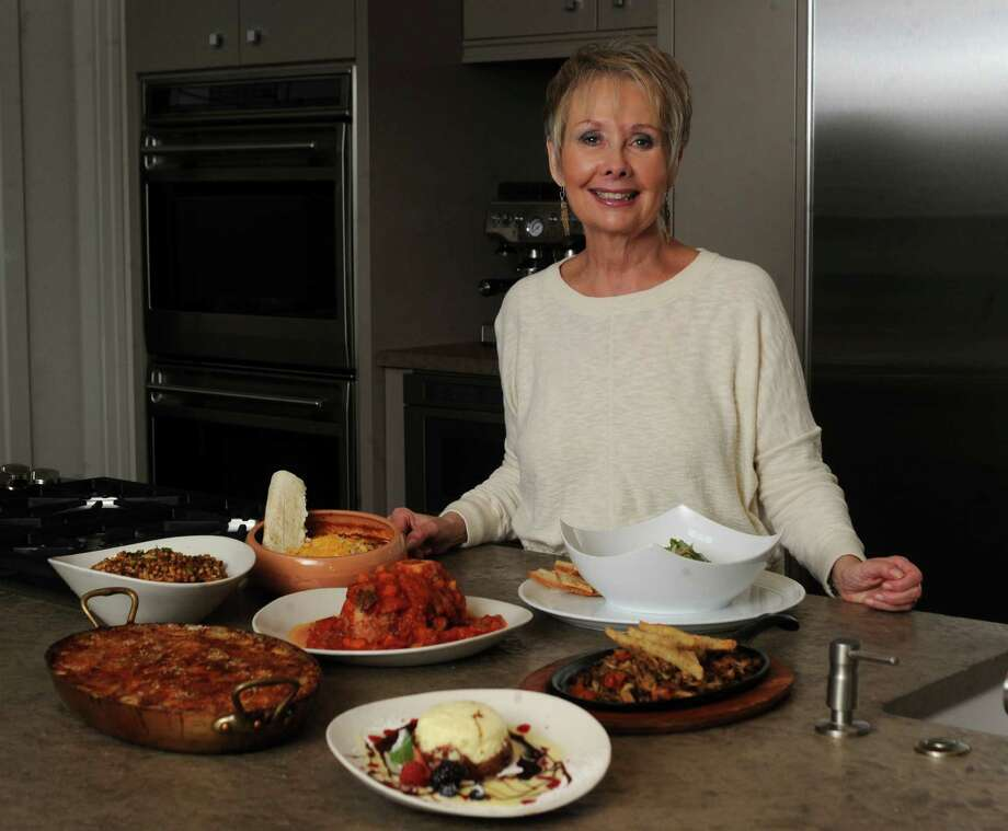 Pat Mozersky is celebrating 20 years as Chefs Secrets columnist. She is surrounded by some of her favorite dishes. Clockwise from bottom, a chocolate terrine dessert, Potato gratin from Bistro Vitel, farro sald from Chef Jason Dady's restaurant Tre Trattoria, Cortez family chili from Mi Tierra, La Margarita and Pico de Gallo, osso buco from Paesano's, ceviche from from Sandbar Fish House and Market, expensive mushrooms dish rom Biga on the Banks. April 26, 2012. Billy Calzada / San Antonio Express-News Photo: BILLY CALZADA, San Antonio Express-News / SAN ANTONIO EXPRESS-NEWS