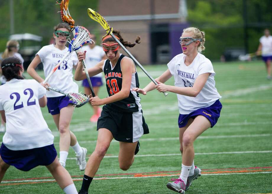 Stamford's Lauren Schapiro cuts through Westhill defenders Lindsay Bagwin, left, and Stephanie Roones as Westhill High School hosts Stamford in a lacrosse game in Stamford, Conn., Sunday, May 1, 2012. Photo: Keelin Daly / Stamford Advocate