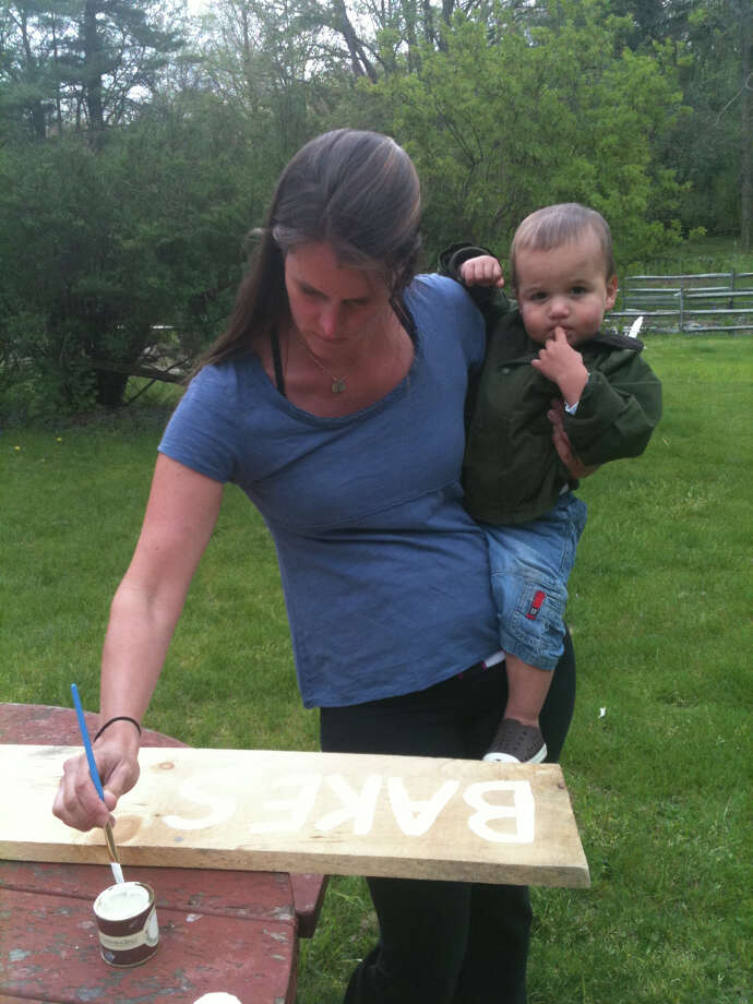 Nature Center Preschool mother Ainsley Hayes and her son, James, paint signs for the Garden Fest event on May 5. Photo: Contributed Photo