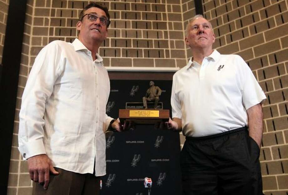 Spurs head coach Gregg Popovich (right) receives the Red Auerbach trophy for being chosen as the 2011-12 NBA coach of the year on Tuesday, May 1, 2012. Popovich was joined by his staff along with Spurs General Manager R.C. Buford (left) for the announcement at their training facility. Kin Man Hui/Express-News. (KIN MAN HUI / SAN ANTONIO EXPRESS-NEWS)
