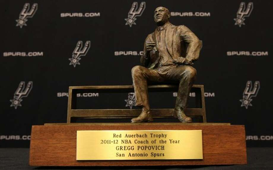Spurs head coach Gregg Popovich receives the Red Auerbach trophy for being chosen as the 2011-12 NBA coach of the year on Tuesday, May 1, 2012. Popovich was joined by his staff along with Spurs General Manager R.C. Buford for the announcement at their training facility. Kin Man Hui/Express-News. (KIN MAN HUI / SAN ANTONIO EXPRESS-NEWS)