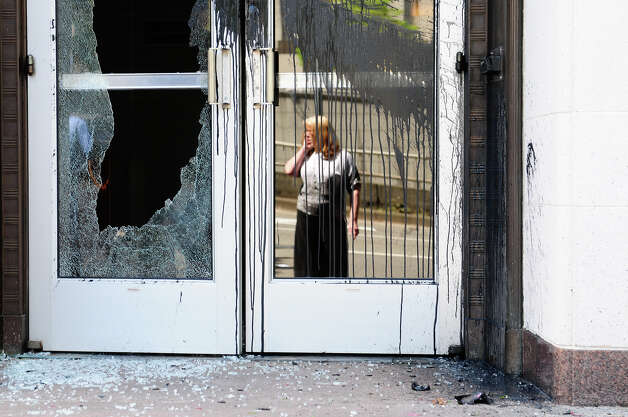 A woman talks on her cellphone as she looks at the damage to the Federal Courthouse in Seattle on Tuesday, May 1, 2012. A small group of protesters dressed in black grew violent in the early afternoon, using flagpoles, rocks and paint bombs to damage local businesses downtown. Photo: LINDSEY WASSON / SEATTLEPI.COM
