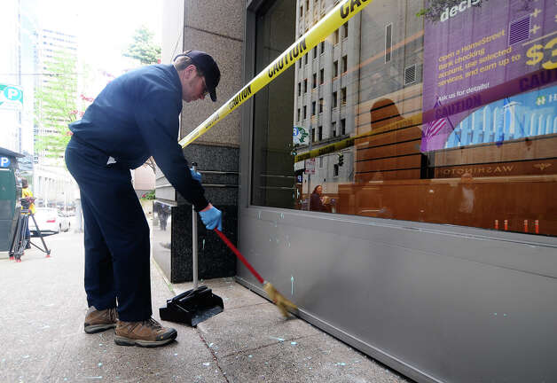 An HSBC bank employee sweeps up broken window glass at Union and 6th Ave. in Seattle on Tuesday, May 1, 2012. A small group of protesters dressed in black grew violent in the early afternoon, using flagpoles, rocks and paint bombs to damage local businesses downtown. Photo: LINDSEY WASSON / SEATTLEPI.COM