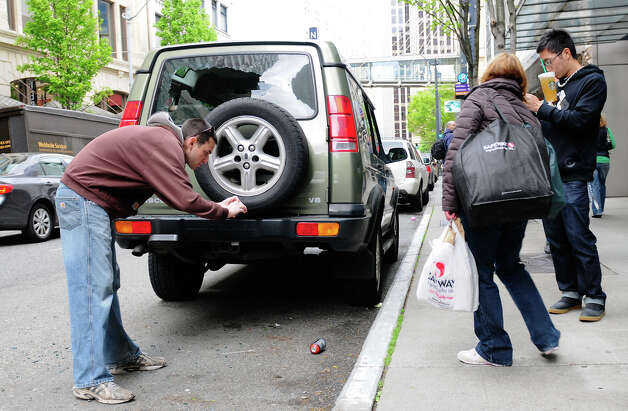 People take photos of a discarded spray paint can and a vandalized car  at 6th Avenue and Pike Street. Photo: LINDSEY WASSON / SEATTLEPI.COM