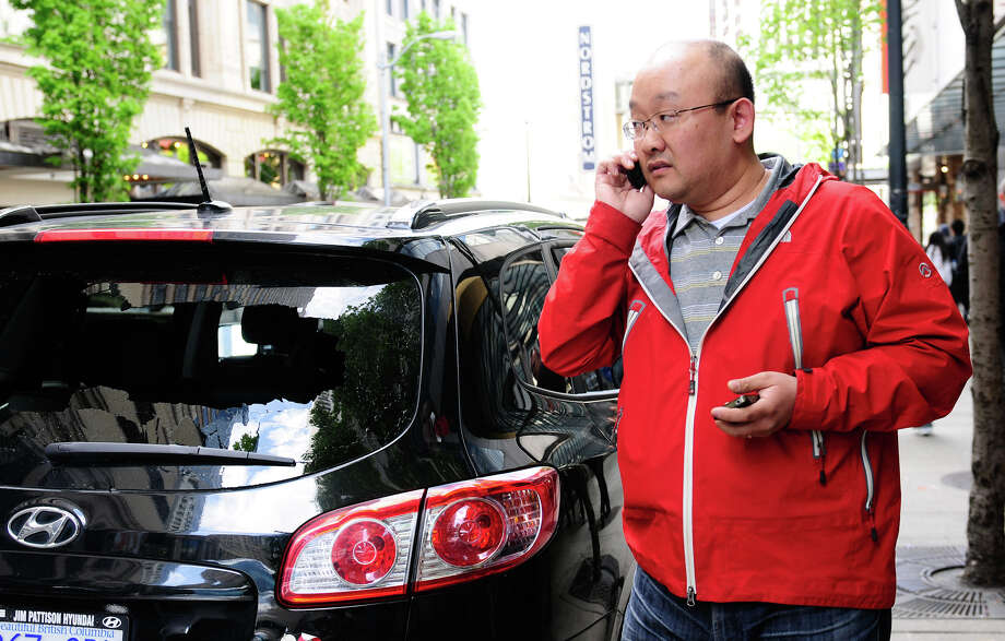 A tourist from Vancouver, B.C. who identified himself only as Sam, talks on the phone after finding his car vandalized by protesters. Photo: LINDSEY WASSON / SEATTLEPI.COM