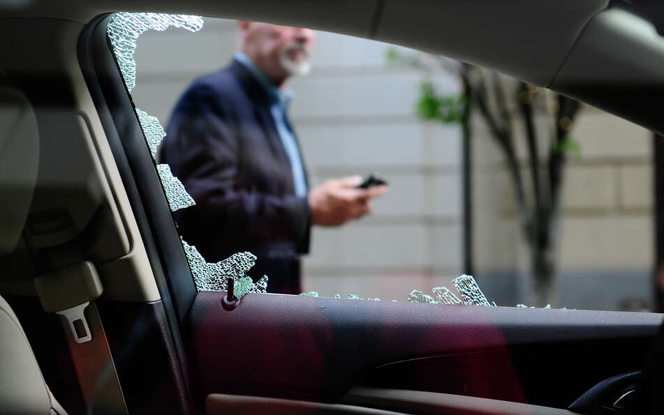 A man walks by a vandalized car.