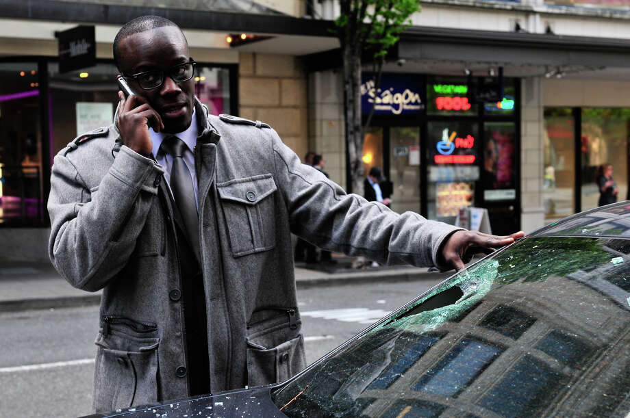 A man talks on the phone as he surveys the damage to his car. Photo: LINDSEY WASSON / SEATTLEPI.COM