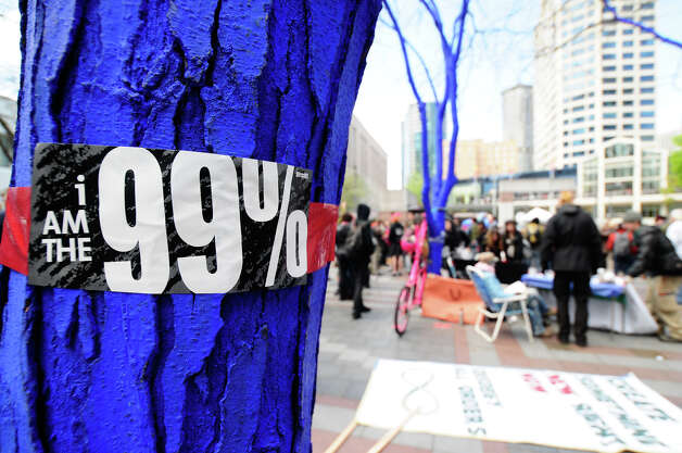 A 99% sticker is shown on a tree painted blue, part of an art project, at Westlake Park. Photo: LINDSEY WASSON / SEATTLEPI.COM