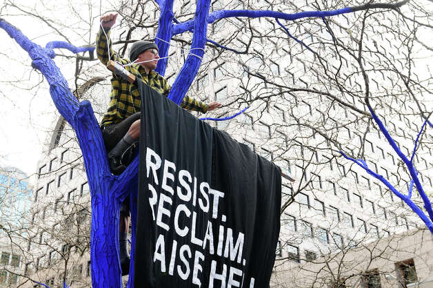 A May Day protester helps hang a large cloth sign on a tree at Westlake Park. Photo: LINDSEY WASSON / SEATTLEPI.COM