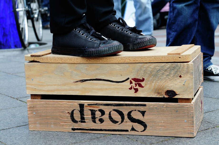 "A protester stands on a ""soap"" box at Westlake Park. Photo: LINDSEY WASSON / SEATTLEPI.COM"