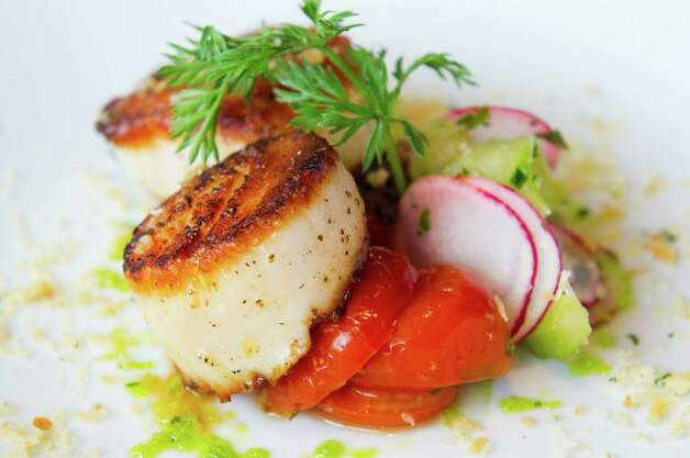 Seared scallops served with tomato, bacon jam and celery slaw at ...