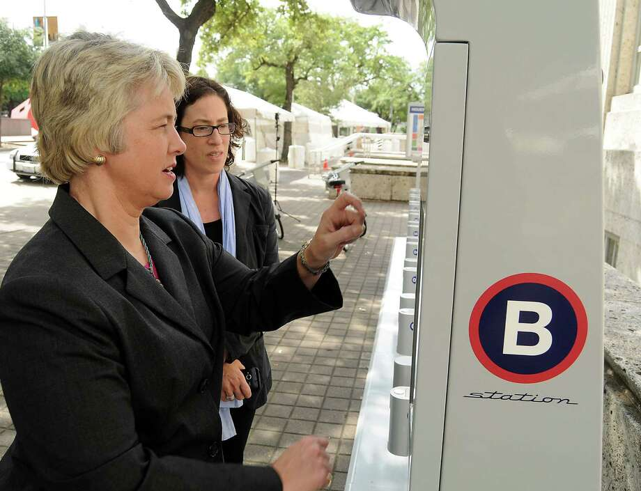 "Under the watchful eye of sustainability director Laura Spanjian, Mayor Annise Parker tests out the self-service B-cycle station outside City Hall. Spanjian noted that ""the love affair with the car is finally over."" Photo: Dave Rossman / © 2012 Dave Rossman"