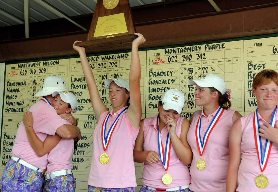 Montgomery Head Golf Coach Rusty Herridge, from left, hugs senior Abbey Bradley while teammates Kirby Sullivan, Kallie Gonzales, Laura Lindsey, and Paige Roberts  show their excitement during the trophy presentation at the Class 4A state golf championship at Jimmy Clay Golf Course in Austin on Tuesday. Photo: Jerry Baker, For The Chronicle