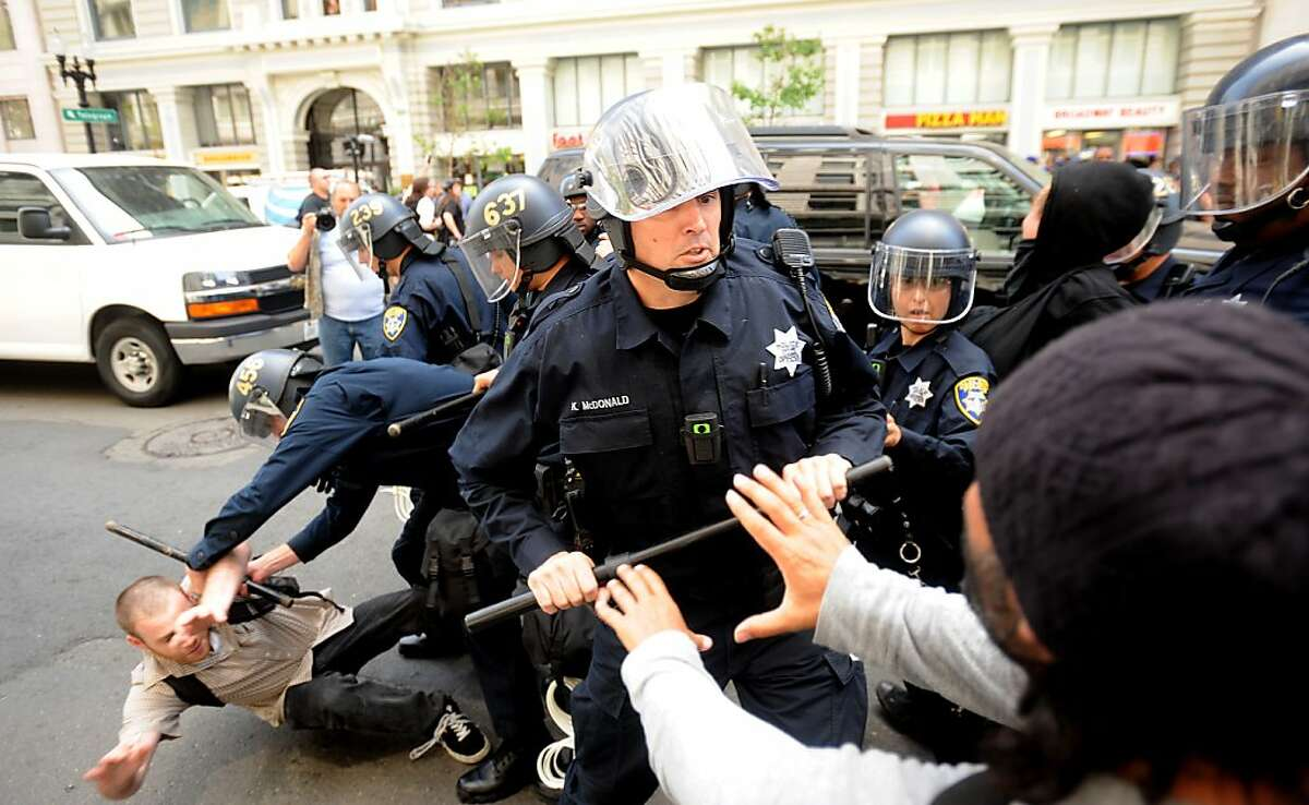 Police scuffle with Occupy Oakland protesters near Broadway and 14th St. on Tuesday, May 1, 2012, in Oakland, Calif.