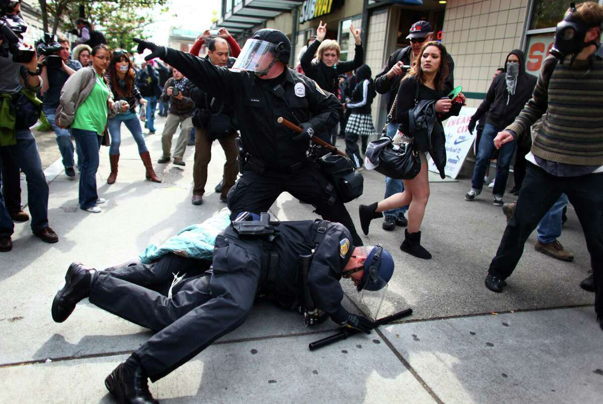 Officers arrest a man that threw a glass jar and hit an officer in his face shield during a May Day rally on Tuesday, May 1, 2012 in downtown Seattle. The rally turned violent when black-clad protesters smashed windows and threw objects at police. One officer was hit in the head with a glass bottle.