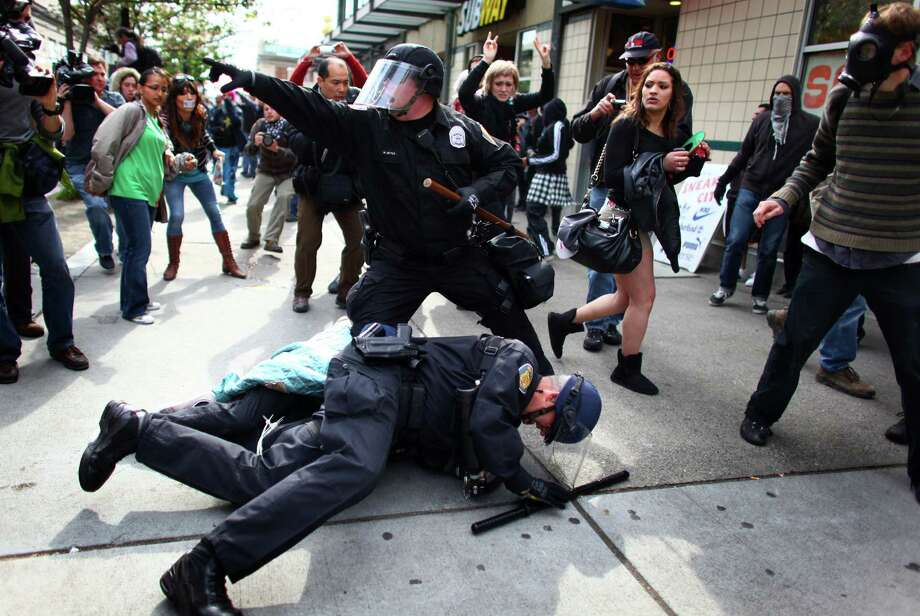 Officers arrest a man that threw a glass jar and hit an officer in his face shield during a May Day rally on Tuesday, May 1, 2012 in downtown Seattle. The rally turned violent when black-clad protesters smashed windows and threw objects at police. One officer was hit in the head with a glass bottle. Photo: JOSHUA TRUJILLO / SEATTLEPI.COM
