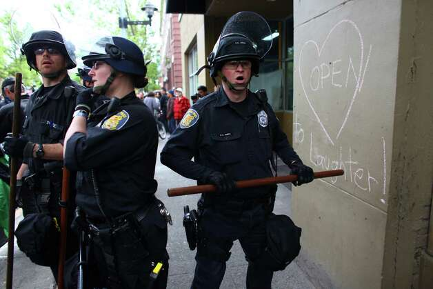 Officers try to clear a an area during a May Day rally on Tuesday. The rally turned violent when black-clad protesters smashed windows and threw objects at police. Photo: JOSHUA TRUJILLO / SEATTLEPI.COM