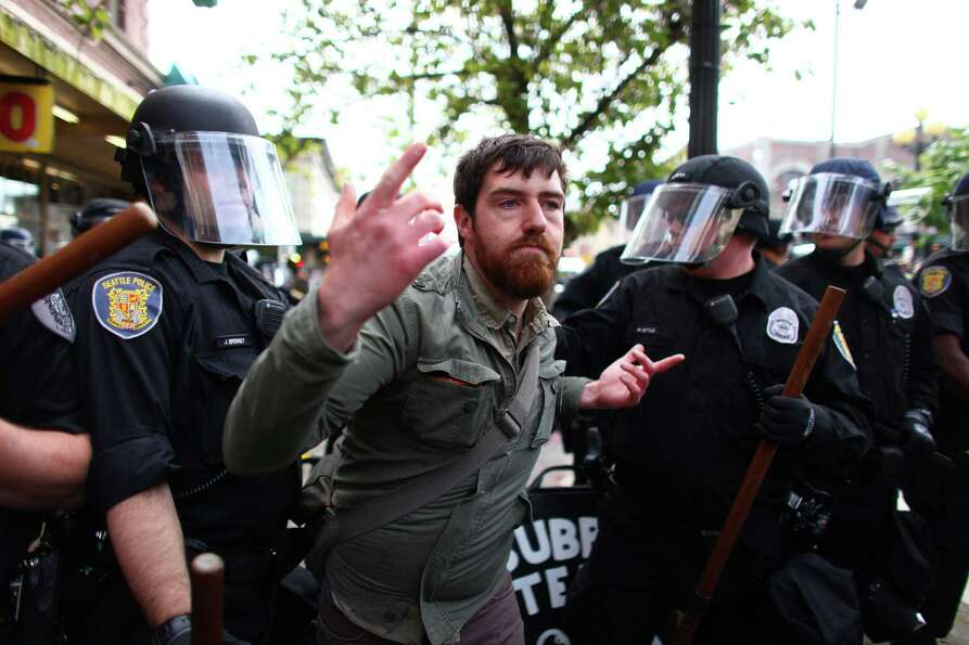 A man is shoved by officer during a May Day rally near Pike Place Market.