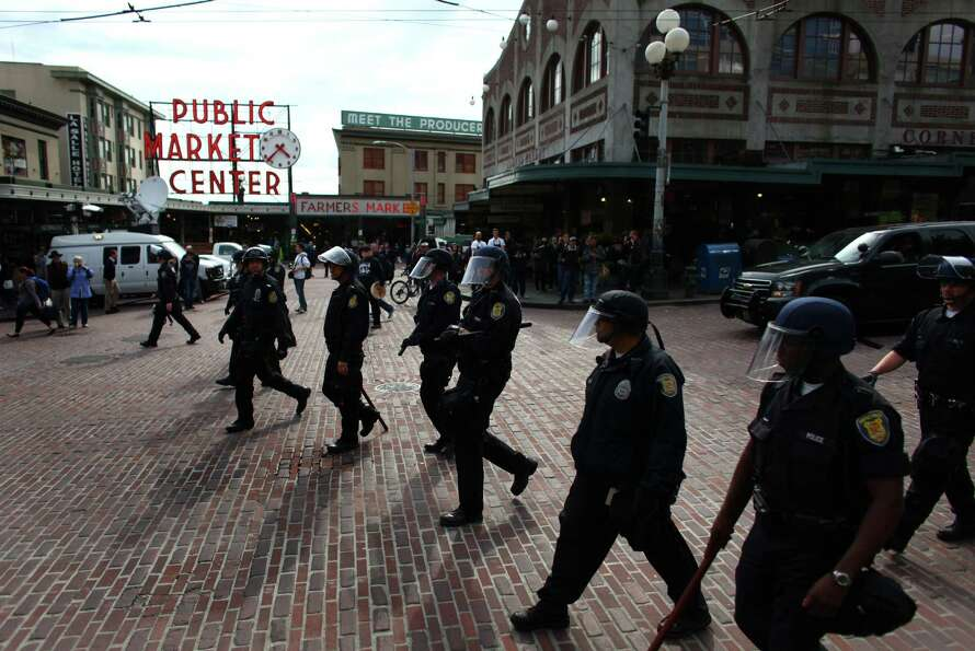 Officers march past the Pike Place Market during a May Day rally.