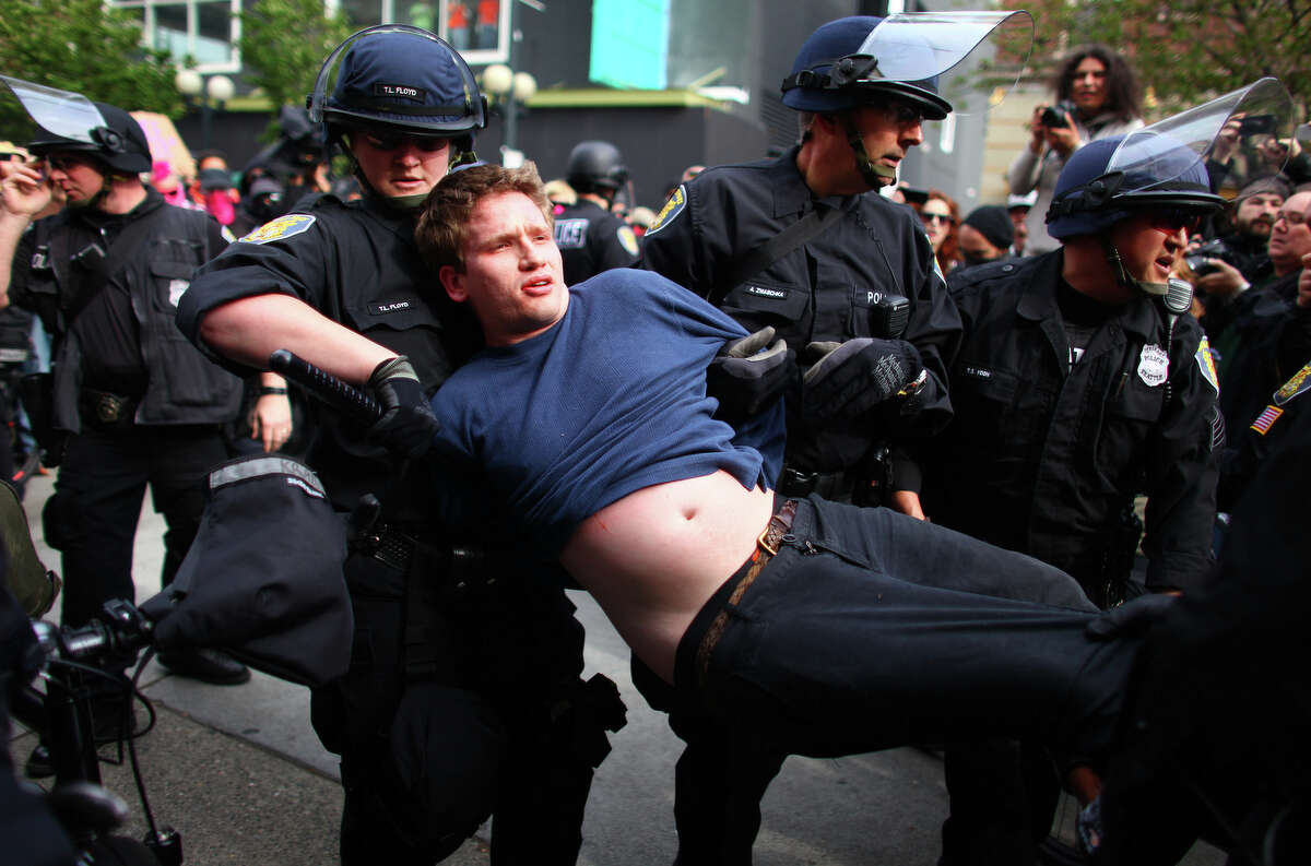 A man that was seen throwing a glass jar that hit an officer square in his face shield is carried away during a May Day rally.