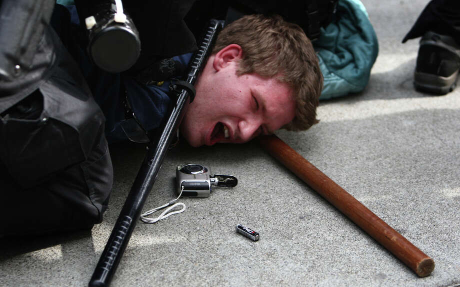 A man that was seen hitting an officer in his face shield with a glass jar is taken down by officers during a May Day rally on Tuesday. The rally turned violent when black-clad protesters smashed windows and threw objects at police. Photo: JOSHUA TRUJILLO / SEATTLEPI.COM