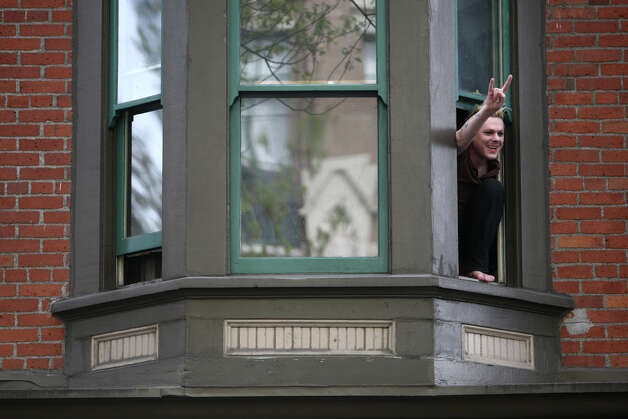 A man acknowledges marchers from an apartment building in Belltown. Photo: JOSHUA TRUJILLO / SEATTLEPI.COM
