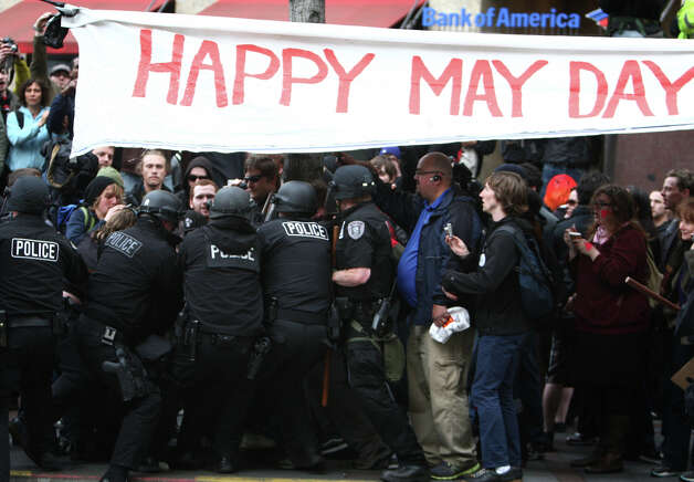 Police and protesters push and shove during a May Day rally on Tuesday, May 1, 2012 in downtown Seattle. The rally turned violent when black-clad protesters smashed windows and threw objects at police. One officer was hit in the head with a glass bottle. Photo: JOSHUA TRUJILLO / SEATTLEPI.COM