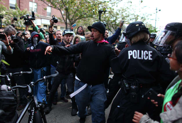 Police and protesters shove and push during a May Day rally on Tuesday, May 1, 2012 in downtown Seattle. The rally turned violent when black-clad protesters smashed windows and threw objects at police. One officer was hit in the head with a glass bottle. Photo: JOSHUA TRUJILLO / SEATTLEPI.COM