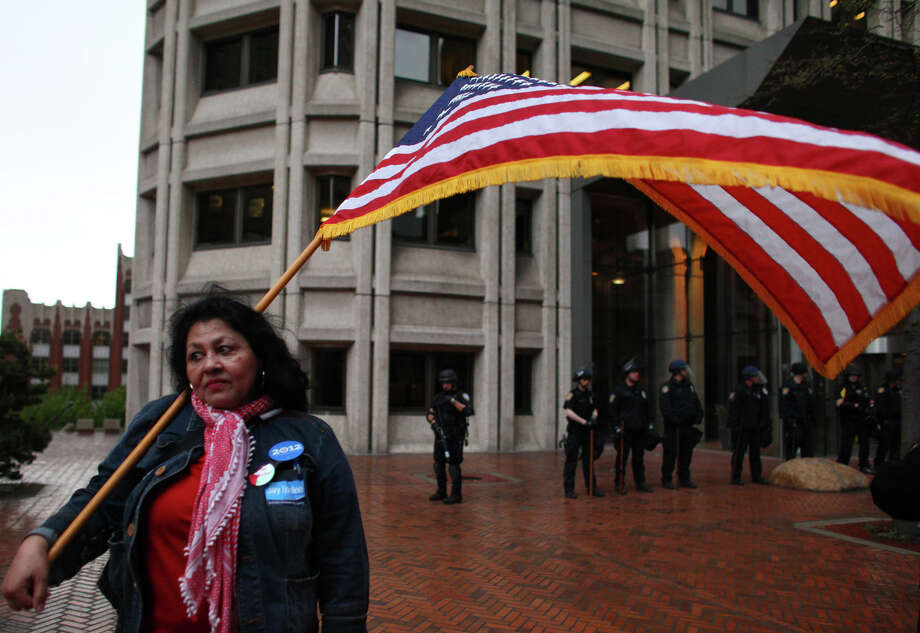 Antonia Gonzalez, part of an immigrant rights rally, holds a flag outside the Seattle Federal Building. The immigrant rights rally was largely eclipsed by an earlier violent march by black-clad protesters. Photo: JOSHUA TRUJILLO / SEATTLEPI.COM