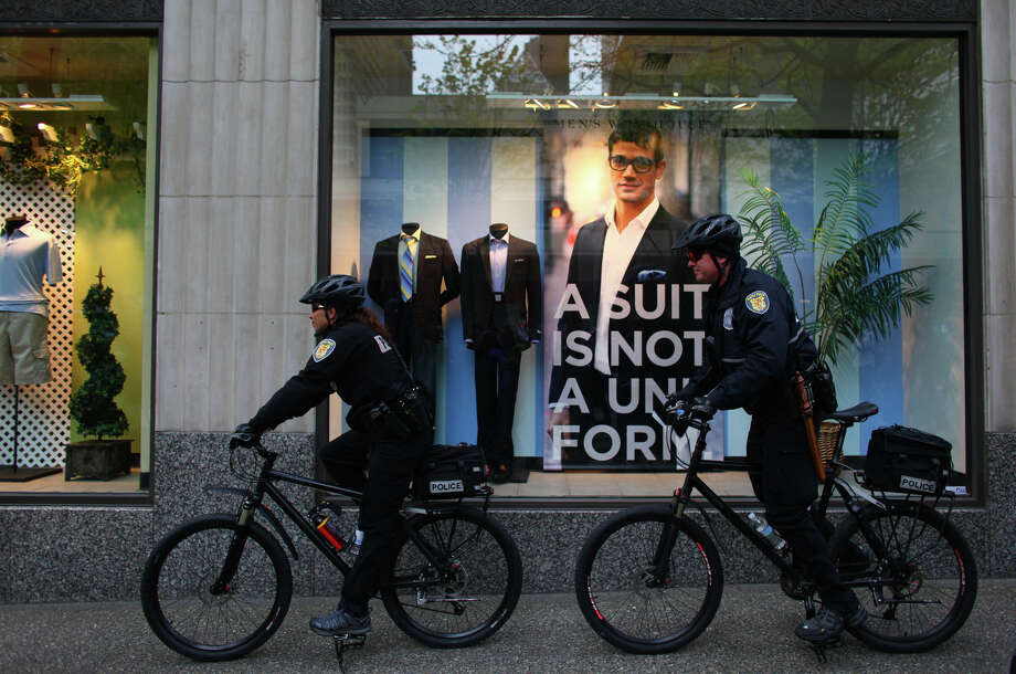 Police officers ride past a window display during a May Day rally. Photo: JOSHUA TRUJILLO / SEATTLEPI.COM