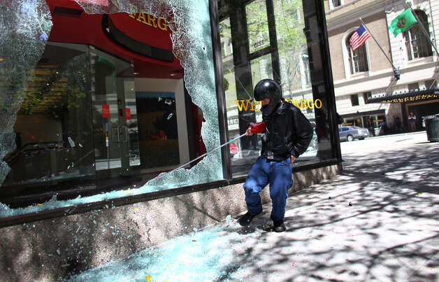 A black-clad protester breaks a window at a Wells Fargo branch. Photo: JOSHUA TRUJILLO / SEATTLEPI.COM