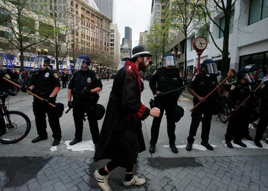 A protester dressed as a clown walks in front of police in Westlake Park. Photo: SOFIA JARAMILLO / SEATTLEPI.COM