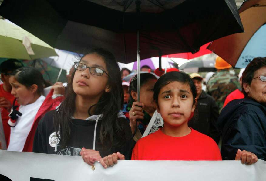 Joselyn Ortega and Erandy Flores listen to a speaker during a rally for immigrants rights. The peace