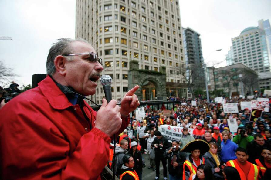 A speaker addresses a crowd in front of the Wells Fargo building during an immigrant rights march, a