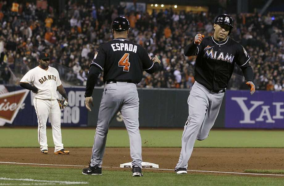 Miami Marlins' Giancarlo Stanton, right, celebrates with third base coach Joey Espada (4) after hitting a solo home run off of San Francisco Giants pitcher Matt Cain during the fifth inning of a baseball game in San Francisco, Tuesday, May 1, 2012. At left is Giants third baseman Pablo Sandoval. (AP Photo/Jeff Chiu) Photo: Jeff Chiu, Associated Press