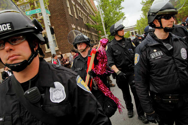 Police Officers confiscate wooden poles during a May Day rally on Tuesday, May 1, 2012 in downtown Seattle. Photo: JOE DYER / SEATTLEPI.COM