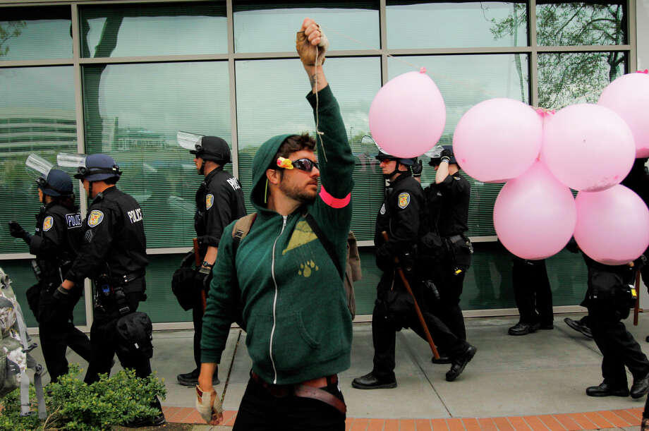 A protester holds balloons during a march. Photo: JOE DYER / SEATTLEPI.COM