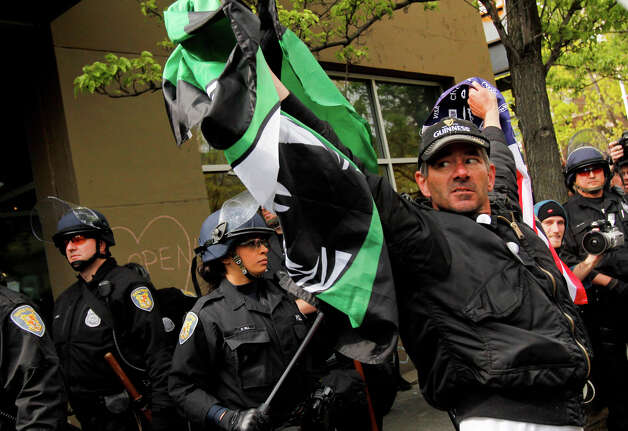 A man holds flags during a May Day rally. Photo: JOE DYER / SEATTLEPI.COM