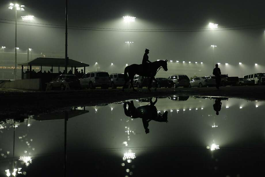 An exercise rider walks a horse off the track at Churchill Downs after a morning workout Tuesday, May 1, 2012, in Louisville, Ky. (AP Photo/Charlie Riedel) Photo: Charlie Riedel, Associated Press