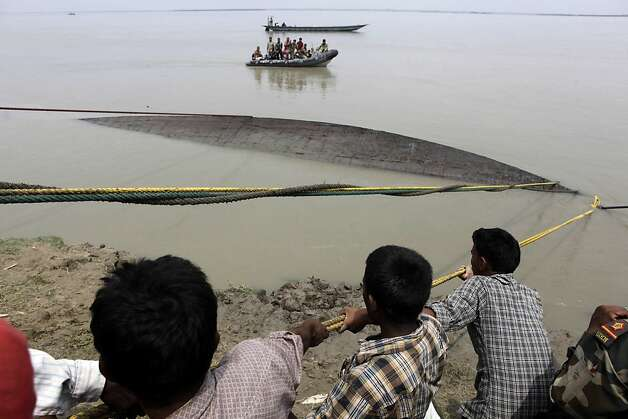 Rescuers pull out the wreckage of a ferry that capsized in the Brahmaputra River at Buraburi village, about 350 kilometers (215 miles) west of the state capital Gauhati, India, Tuesday, May 1, 2012. Army divers and rescue workers pulled more than 100 bodies out of a river after a packed ferry capsized in heavy winds and rain in remote northeast India, an official said Tuesday. At least 100 people were still missing Tuesday after the ferry carrying about 350 people broke into two pieces late Monday, said Pritam Saikia, the district magistrate of Goalpara district. (AP Photo/Anupam Nath) Photo: Anupam Nath, Associated Press