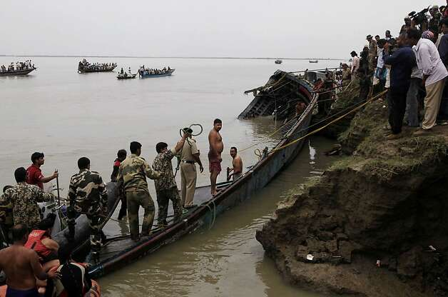 Rescuers pull out a ferry that capsized in the Brahmaputra River at Buraburi village, about 350 kilometers (215 miles) west of the state capital Gauhati, India, Tuesday, May 1, 2012. Army divers and rescue workers pulled more than 100 bodies out of a river after a packed ferry capsized in heavy winds and rain in remote northeast India, an official said Tuesday. At least 100 people were still missing Tuesday after the ferry carrying about 350 people broke into two pieces late Monday, said Pritam Saikia, the district magistrate of Goalpara district. (AP Photo/Anupam Nath) Photo: Anupam Nath, Associated Press