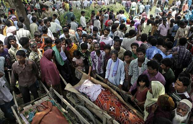 Indian villagers stand near the dead bodies of passengers who died after a ferry capsized in the Brahmaputra River at Buraburi village, about 350 kilometers (215 miles) west of the state capital Gauhati, India, Tuesday, May 1, 2012. Army divers and rescue workers pulled more than 100 bodies out of a river after a packed ferry capsized in heavy winds and rain in remote northeast India, an official said Tuesday. At least 100 people were still missing Tuesday after the ferry carrying about 350 people broke into two pieces late Monday, said Pritam Saikia, the district magistrate of Goalpara district. (AP Photo/Anupam Nath) Photo: Anupam Nath, Associated Press
