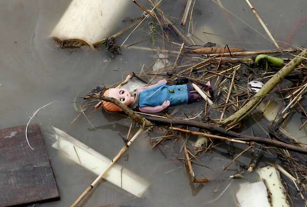 A doll floats with debris in the water after a ferry capsized in the Brahmaputra River at Buraburi village, about 350 kilometers (215 miles) west of the state capital Gauhati, India, Tuesday, May 1, 2012. Army divers and rescue workers pulled more than 100 bodies out of a river after a packed ferry capsized in heavy winds and rain in remote northeast India, an official said Tuesday. At least 100 people were still missing Tuesday after the ferry carrying about 350 people broke into two pieces late Monday, said Pritam Saikia, the district magistrate of Goalpara district. (AP Photo/Anupam Nath) Photo: Anupam Nath, Associated Press
