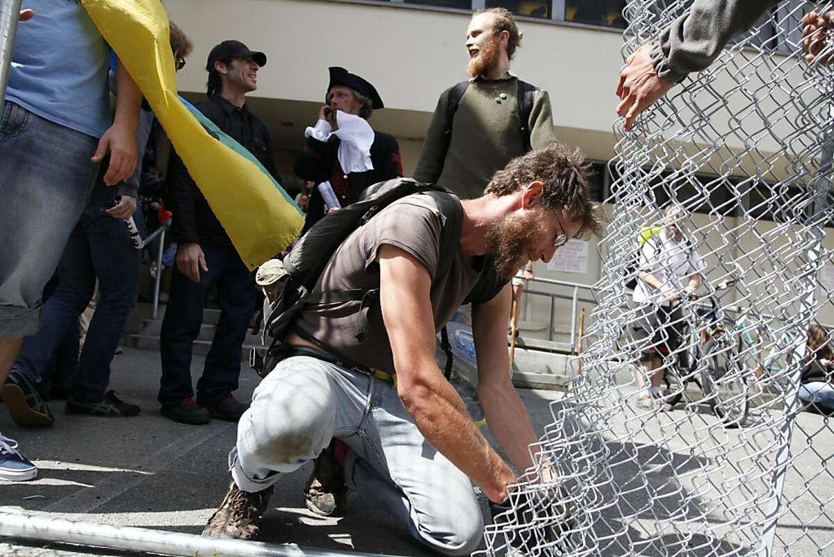 An Occupy SF supporter cuts down a chain link fence surrounding 888 Turk St. in San Francisco Calif. on Tuesday, May 1, 2012. After taking over the vacant building at 888 Turk St. occupiers set up a feeding station.