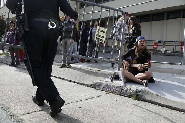 A members of Occupy SF plays the guitar and sings as Police attempt to set up a barricade in front of the vacant building occupiers took over at 888 Turk St. in San Francisco Calif. Tuesday, May 1, 2012. Photo: Alex Washburn