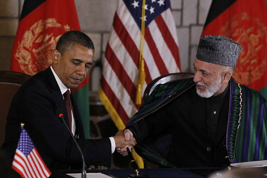 President Barack Obama and Afghan President Hamid Karzai shake hands after making statements before signing a strategic partnership agreement at the presidential palace in Kabul, Afghanistan, Wednesday, May 2, 2012. (AP Photo/Charles Dharapak) Photo: Charles Dharapak, Associated Press